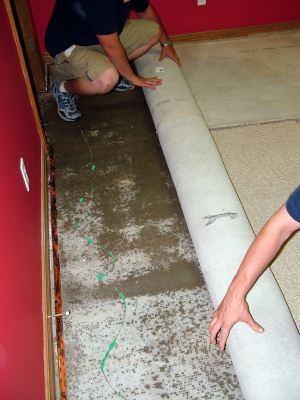 Sewaren water damaged carpet being removed by two men.